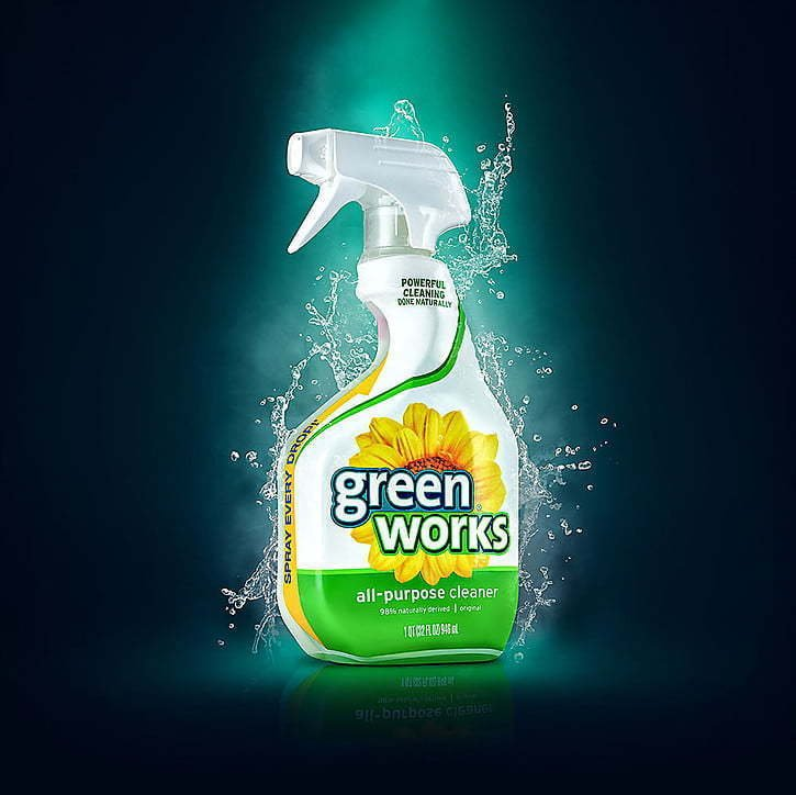 picture of green works bottle with water splash on a blue and green background