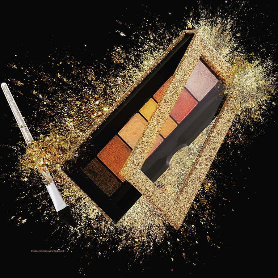 makeup pallet open with gold glitter and makeup brush in air on a black custom photography