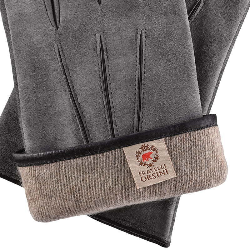 a close-up detail of a pair of light grey gray leather gloves with folded wool lining apparel photography