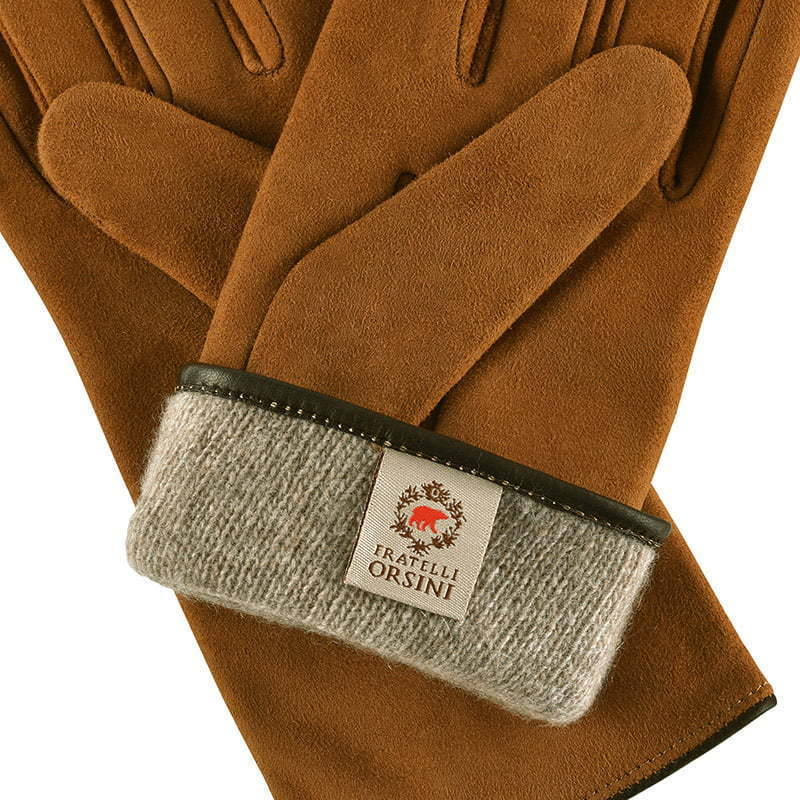 a close-up detail of a pair of light brown leather gloves with folded wool lining apparel photography