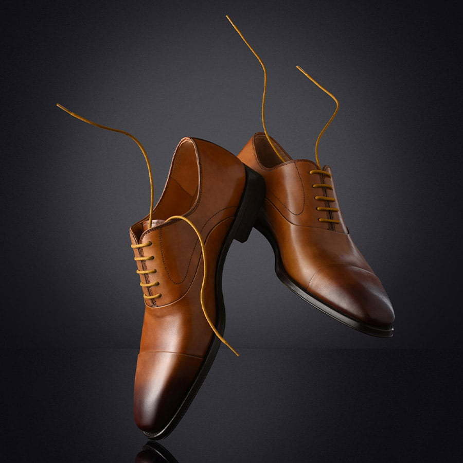 men's brown leather dress shoes with unties laces falling on a dark custom photography