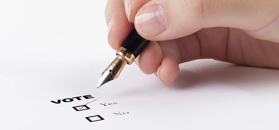 Woman hand voting yes in check-box with blue fountain pen in the air