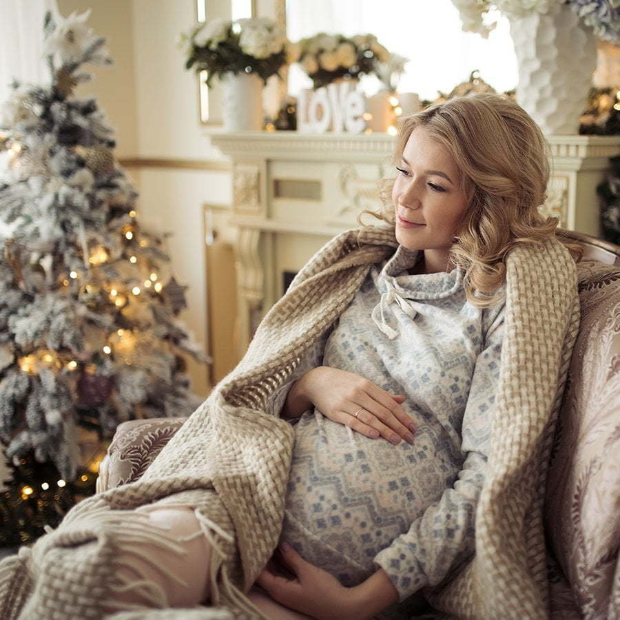 beautiful pregnant woman in comfy clothes. sitting in a chair ne
