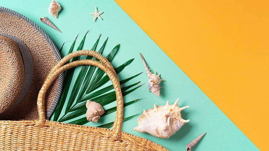 summer fashion flat lay. stylish straw bag, hat, palm leaves, shells on trendy yellow and green background. top view. copy space. sustainable lifestyle