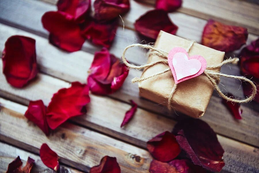 Wrapped gift-box with small pink heart on its top surrounded by rose petals