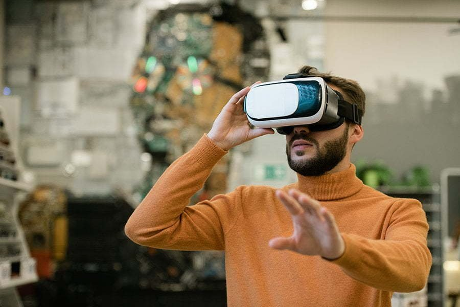young man in virtual reality headset stretching arm towards display