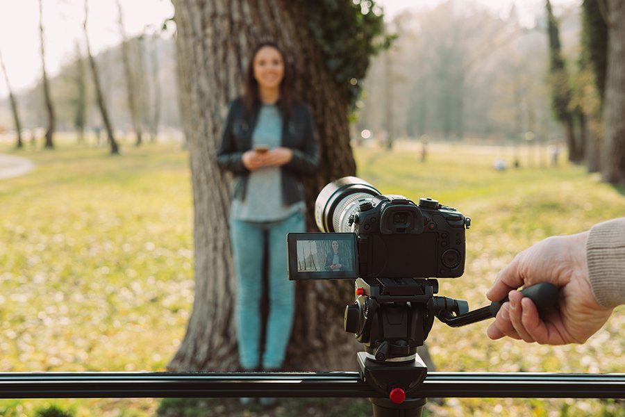 Video shooting at the park: video camera and operator hand on foreground and female model standing in the background