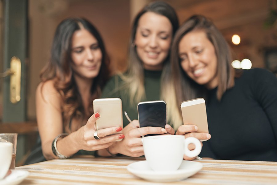 beautiful friends watching social media in a smart phone in a coffee shop.