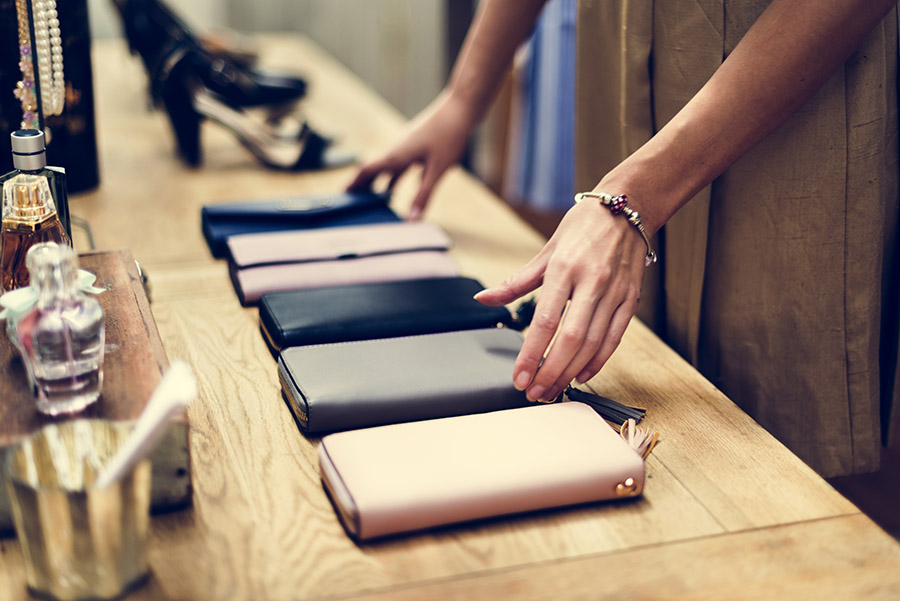 woman adjusting purses for sale