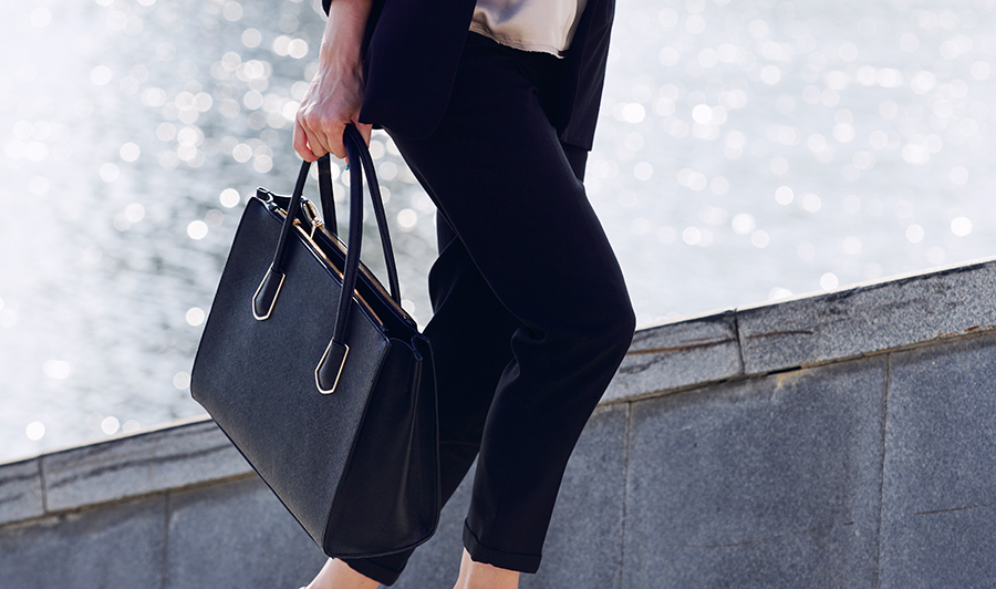 Young elegant businesswoman with black leather handbag moving upstairs in front of camera against riverside and group of modern buildings
