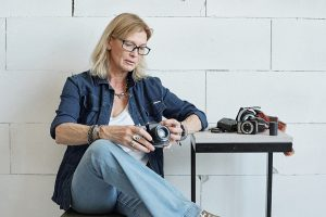 Modern mature lady photographer with blond hair checking camera before photo shoot in studio